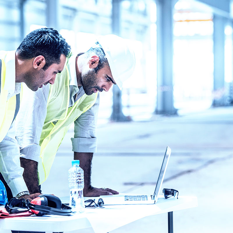 construction workers looking at computer